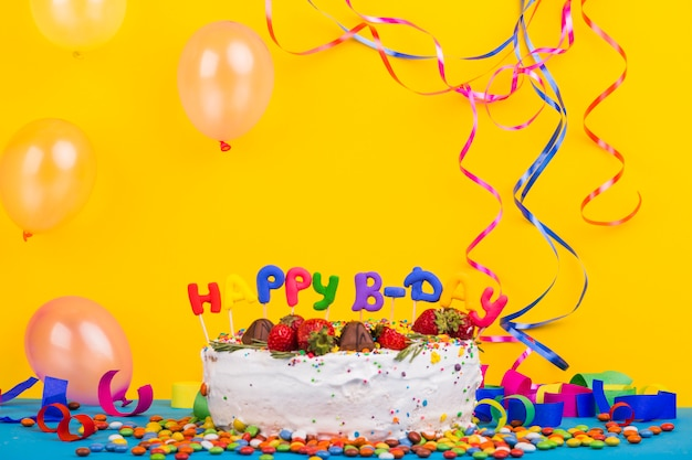 Bolo de aniversário de vista frontal rodeado por elementos de festa