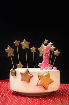 Bolo de aniversário decorado com rosa número 1 e estrelas douradas de gengibre em uma parede escura.