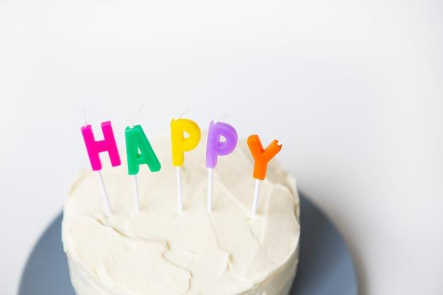 Bolo de aniversário, em um bolo de esponja cremoso a felicidade de inscrição. o conceito de surpresa de feriado e aniversário.