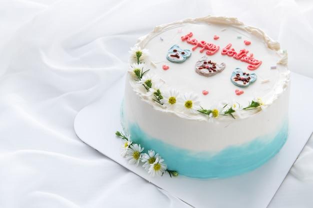 Bolo de aniversário mínimo e gato de rosto bonito decorado e uma pequena flor em cima com fundo de pano branco. sobremesa tailandesa