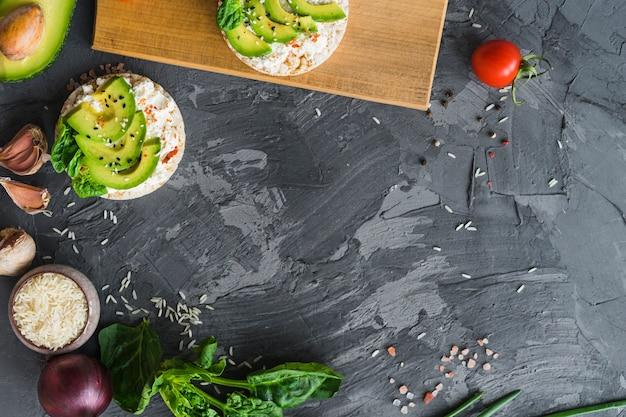 Bolo de arroz com cream cheese; abacate e ingredientes frescos sobre a textura do cimento