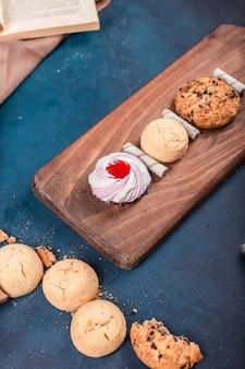 Bolo de baunilha merengue com biscoitos de manteiga e aveia em uma tábua sobre uma mesa azul
