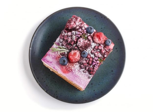 Bolo de berry com creme de leite e geléia de mirtilo no prato de cerâmico azul isolado no fundo branco
