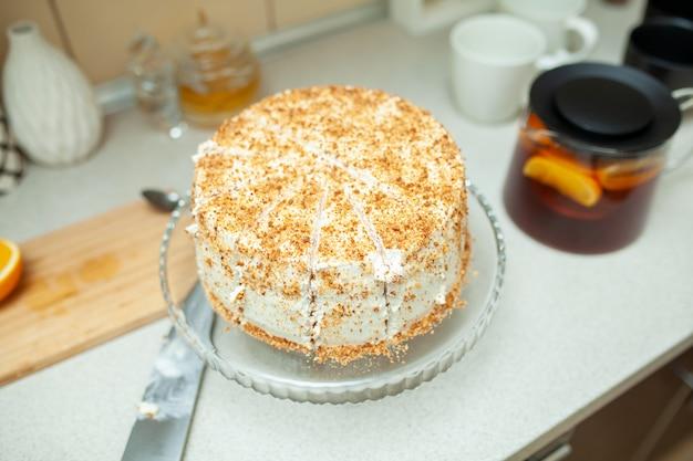 Bolo de biscoito branco cortado em um suporte sobre uma mesa na cozinha.