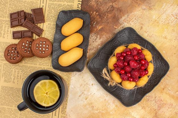 Bolo de biscoito e chá em uma xícara preta na mesa de cores misturadas