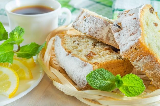 Bolo de biscoito em fatias, uma xícara de chá, fatias de limão e folhas de hortelã
