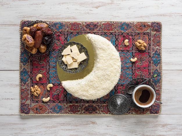 Bolo de biscoito polvilhado com chocolate branco em forma de lua crescente, servido com tâmaras e xícara de café