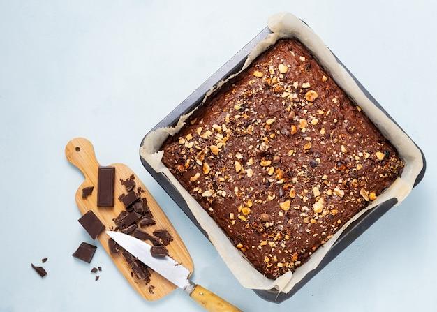 Bolo de brownie de chocolate, sobremesa com nozes e frutas no escuro, diretamente acima. dieta, vegana.