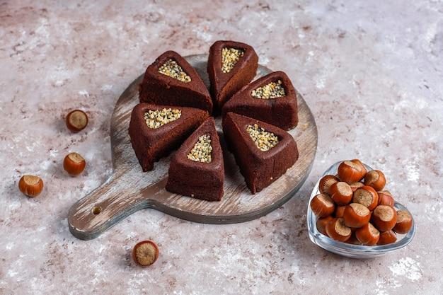 Bolo de brownie fatiado com avelãs.
