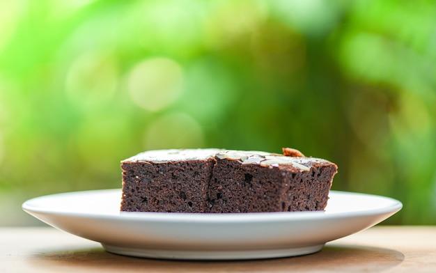 Bolo de brownies na mesa / fatia de bolo de chocolate com porca na madeira e natureza verde