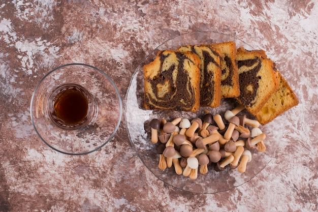 Bolo de cacau com waffles e biscoitos em uma travessa de vidro com um copo de chá, vista de cima
