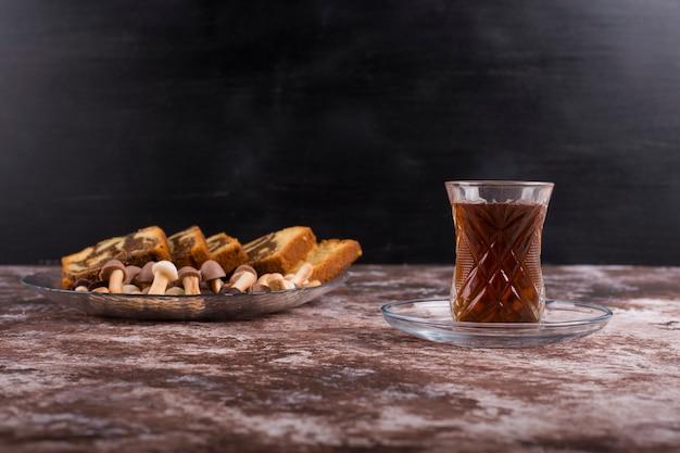 Bolo de cacau com waffles e biscoitos em uma travessa de vidro com um copo de chá