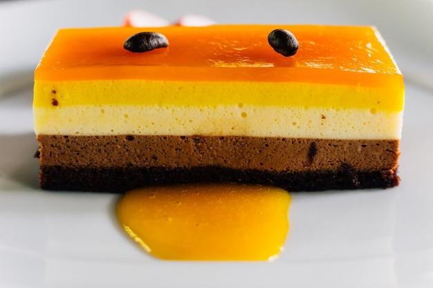 Bolo de camadas incluindo molho de laranja e cobertura de chocolate com sementes de café.