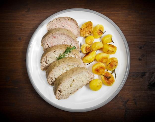 Bolo de carne com batatas assadas no prato