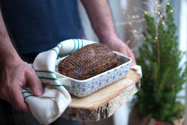 Bolo de carne em uma assadeira, nas mãos de um homem