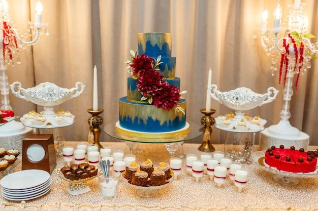 Bolo de casamento azul decorado por flores. desertos. barra de chocolate