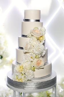 Bolo de casamento bonito festivo decorado com flores isoladas perto acima. bolo de casamento em camadas branco isolado. barra de chocolate na festa de casamento. dia do casamento.