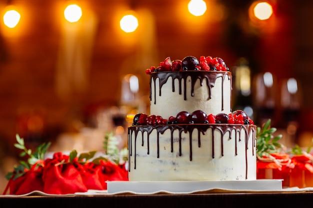 Bolo de casamento branco com dois níveis, decorado com frutas vermelhas e bagas, ensopado em chocolate