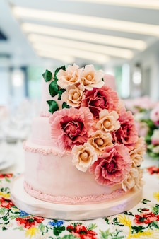 Bolo de casamento branco com flores cor de rosa e verdes em uma mesa festiva com massa. perto do bolo. mesa doce.