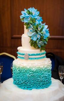 Bolo de casamento branco com flores e mirtilos.