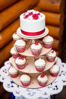 Bolo de casamento branco com uma fita vermelha decorativa