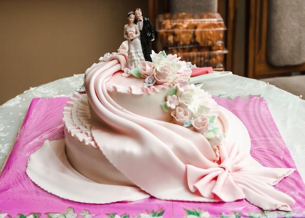 Bolo de casamento branco de duas camadas com uma estatueta de aroeira e noivo como decoração. conceito de casamento.