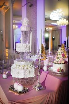 Bolo de casamento branco de três camadas decorado com flores creme em um carrinho.