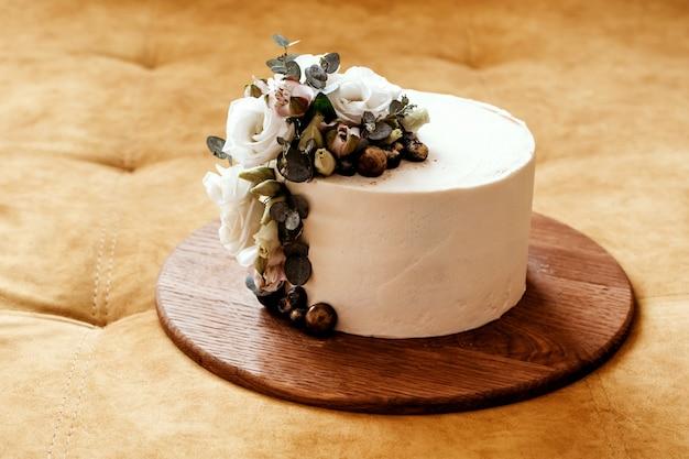 Bolo de casamento branco decorado com flores de eustoma e eucalipto. lugar para texto.