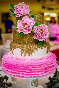 Bolo de casamento branco decorado com peônias de açúcar rosa. a composição de flores
