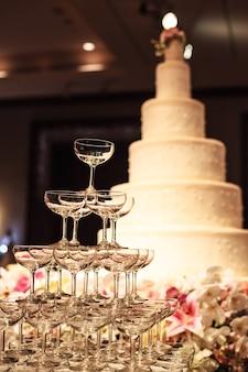 Bolo de casamento com a torre de vidro do champanhe na tabela na fase na cerimônia de casamento.