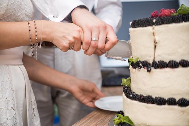 Bolo de casamento com frutas na mesa de madeira. noiva e noivo cortam bolo doce em banquete no restaurante.