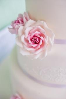 Bolo de casamento de três camadas com rosas rosa feitas de mástique fica em cima da mesa