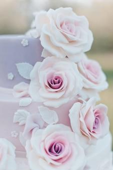 Bolo de casamento em tons pastel decorado com rosas cor de rosa realistas sobre um fundo desfocado do jardim, foco seletivo