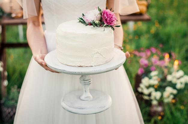 Bolo de casamento nas mãos de noivas