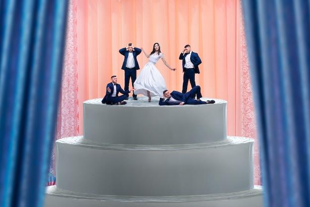 Bolo de casamento, noiva e várias estatuetas de noivos