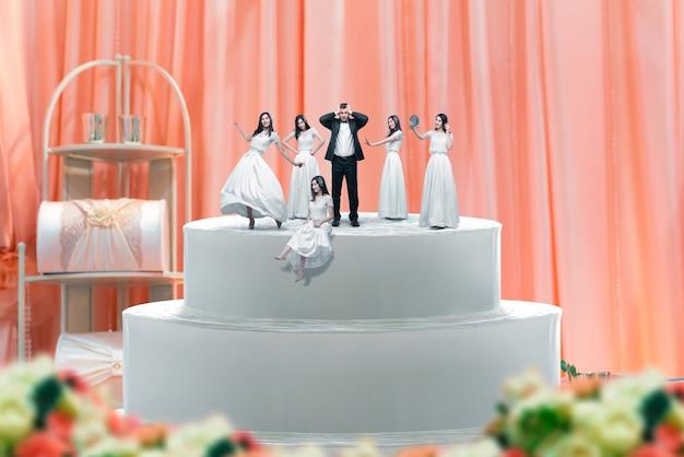 Bolo de casamento, noivo e muitas estatuetas de noivas