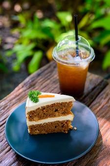 Bolo de cenoura com café em uma mesa de madeira no jardim