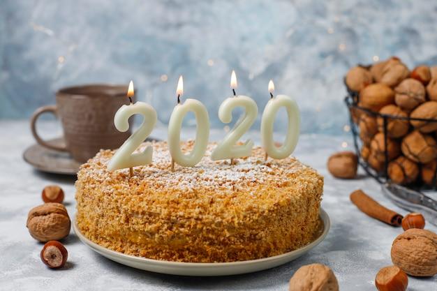 Bolo de cenoura com velas de 2020 e uma xícara de chá em concreto cinza