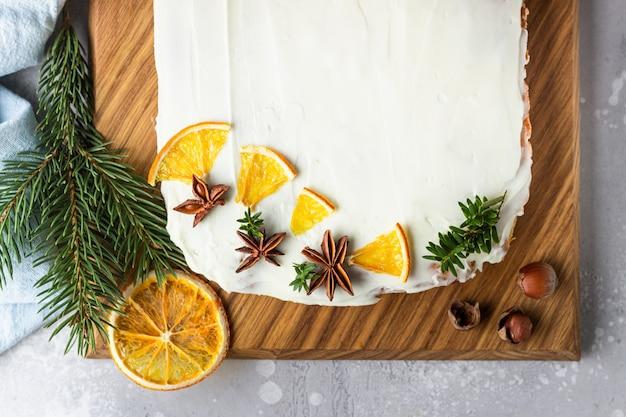 Bolo de cenoura crua com cobertura de cream cheese, fatias de laranja secas e especiarias (canela e anis).