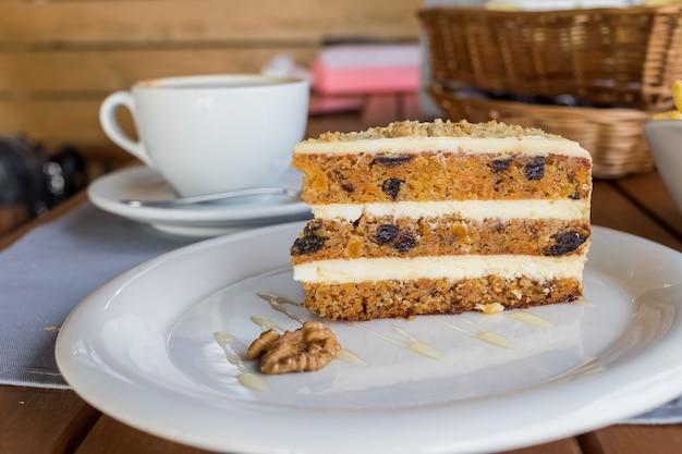 Bolo de cenoura e abóbora com creme de café em um corte no prato. delicioso bolo de cenoura fatiado