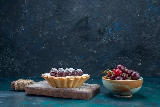 Bolo de cereja com cerejas frescas no escuro