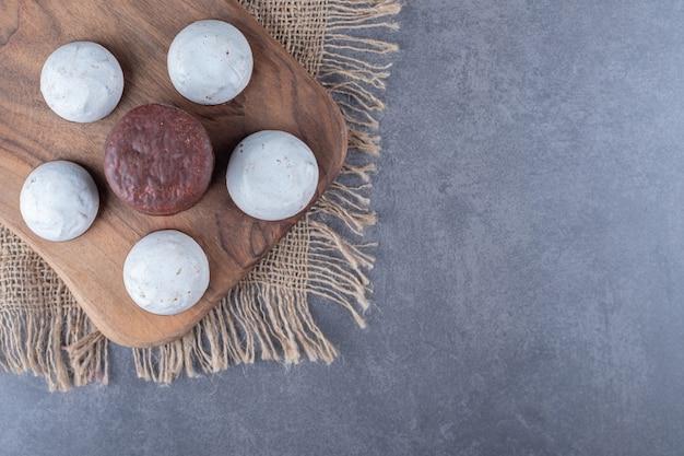 Bolo de chocolate aparece e biscoito a bordo na toalha na mesa de mármore.