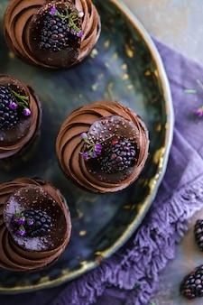 Bolo de chocolate bolos em um prato de barro bonito com amoras por cima como decoração.