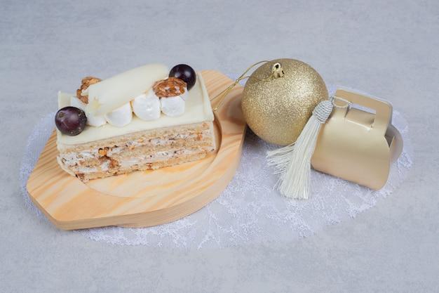 Bolo de chocolate branco na placa de madeira com bola e presente de natal. foto de alta qualidade