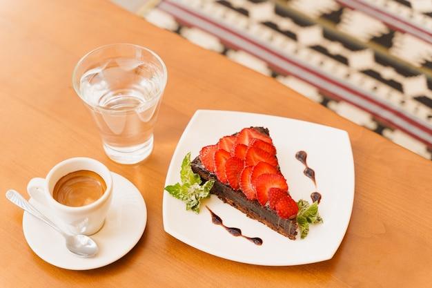 Bolo de chocolate, brownie com morangos e hortelã, expresso, copo de água em uma mesa de madeira