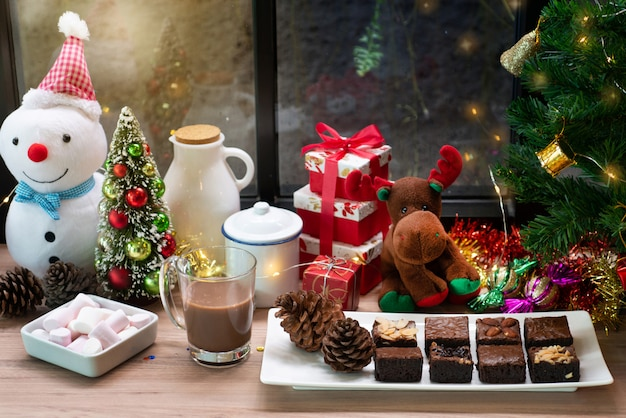 Bolo de chocolate brownie e bebida de chocolate quente na mesa de madeira