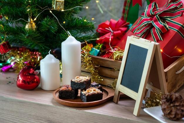 Bolo de chocolate brownie na mesa de madeira, com fundo de decoração de natal