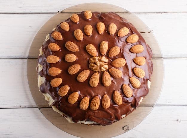 Bolo de chocolate caseiro com amêndoas em fundo branco de madeira
