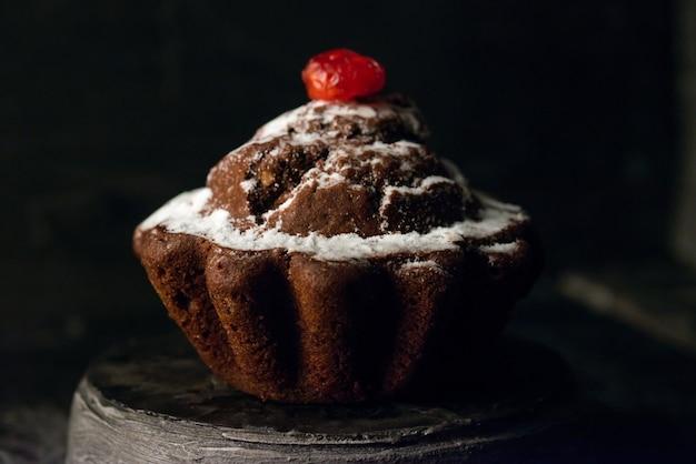 Bolo de chocolate caseiro com cerejas cristalizadas secas e baunilha em pó.