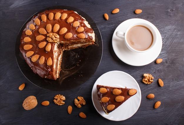Bolo de chocolate caseiro com creme de leite, caramelo e amêndoas em fundo preto de madeira.